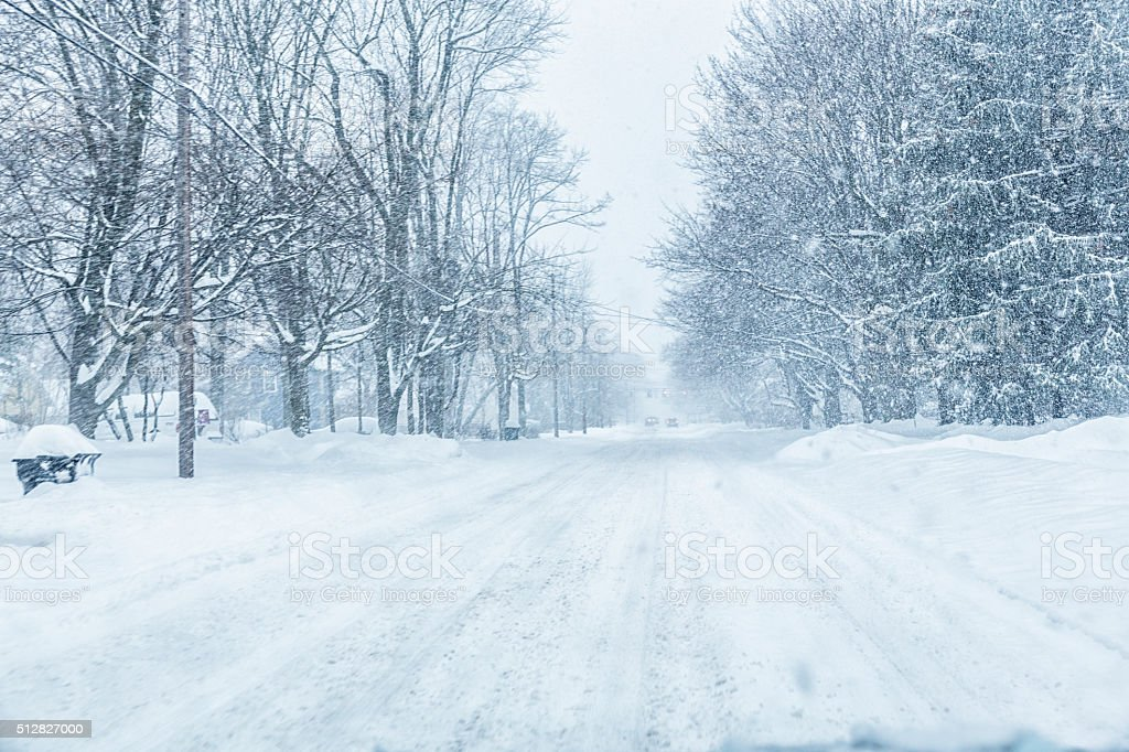 Suburban Road Through Car Windshield During Blizzard Snow Storm stock photo