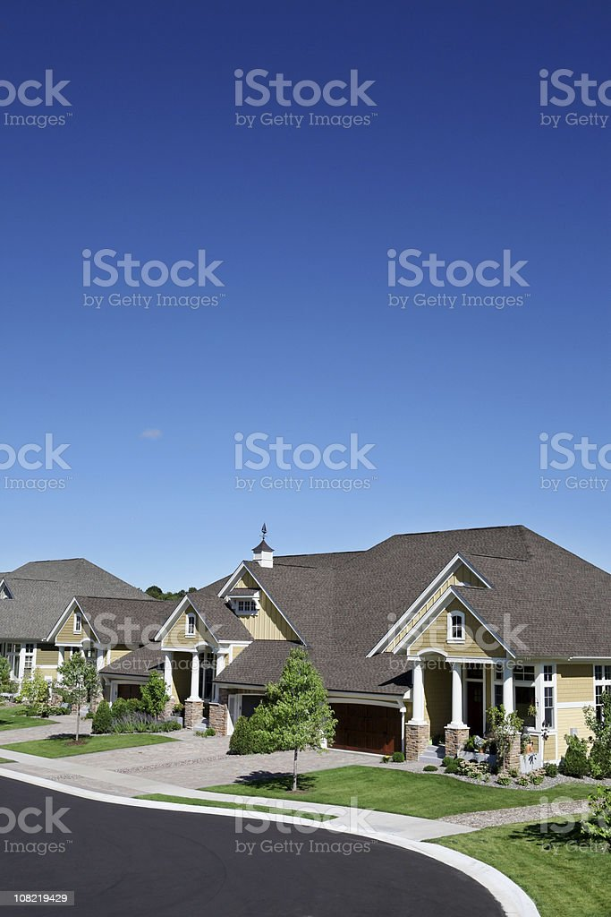 Suburban Street with Manicured Green Lawns and Blue Sky royalty-free stock photo