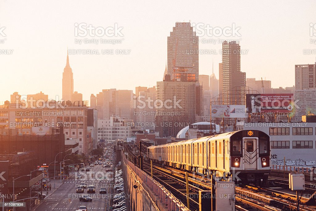NYC Subway Train Drives Toward Queens During Rush Hour Sunset stock photo