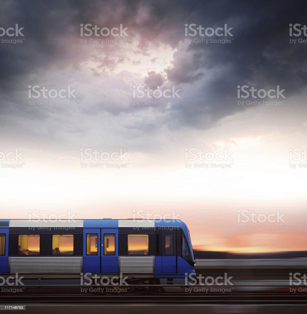 Subway train in profile crossing bridge at sunset royalty-free stock photo
