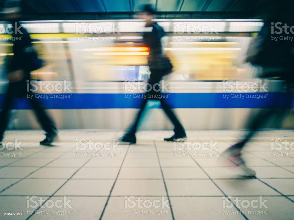 Subway train leaving station. People on platform. stock photo