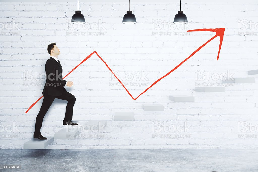 Success concept with businessman climbing the stairs and red arr stock photo