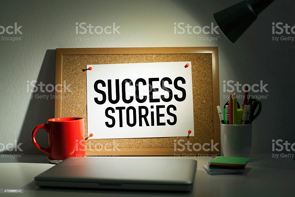 Success stories banner pinned to cork board on desk stock photo