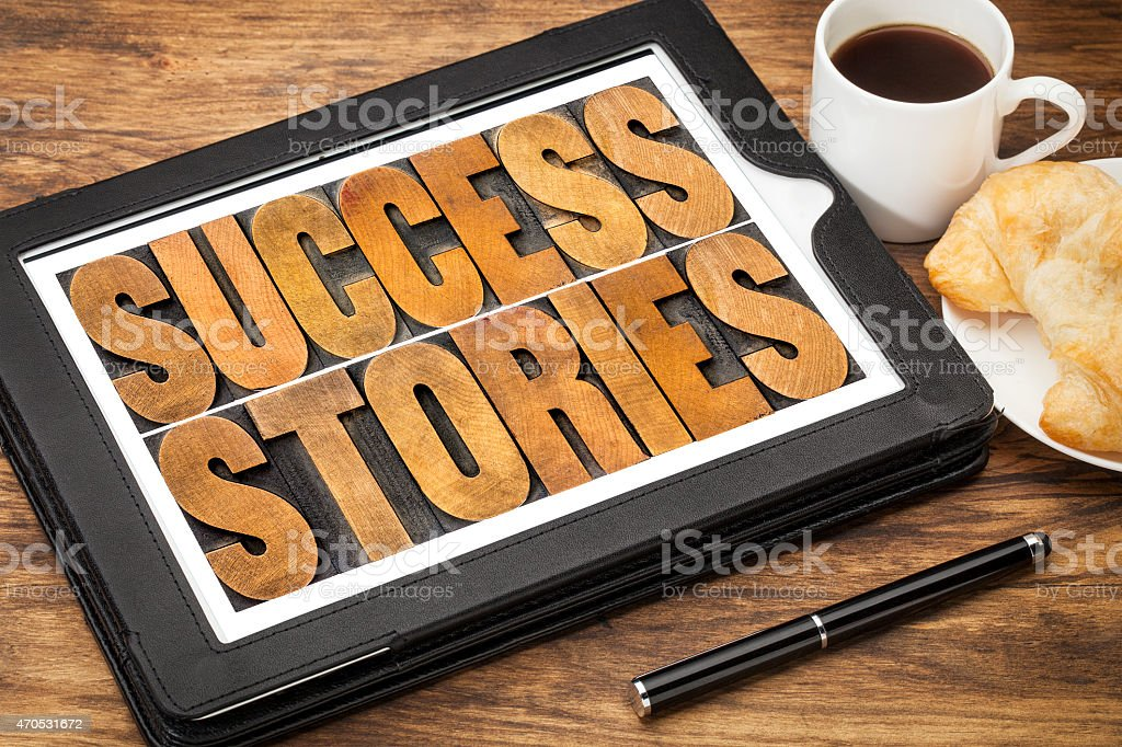 success stories on digital tablet stock photo