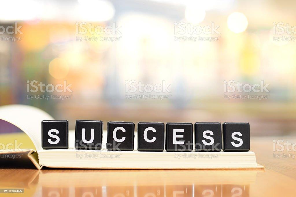 Success word from black plastic blocks on notebook stock photo