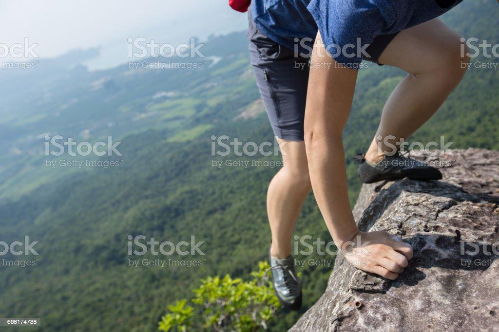 success young woman rock climber on mountain peak stock photo