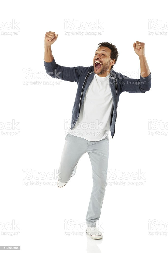 Successful african man celebrating his achievement stock photo