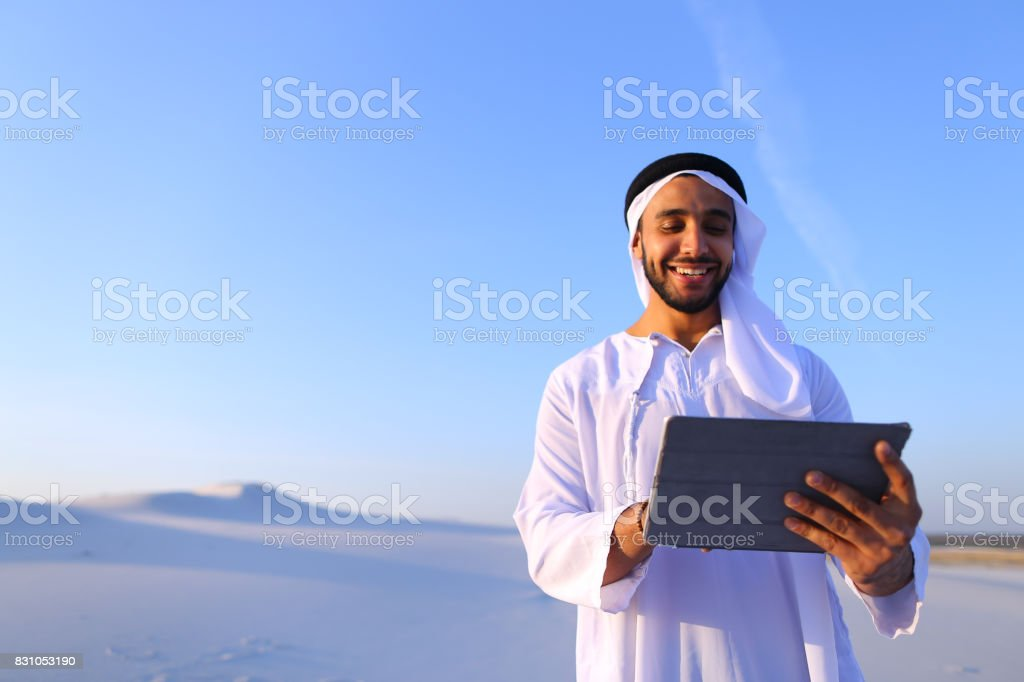 Successful Arabian businessman holds in hands and uses tablet, s stock photo