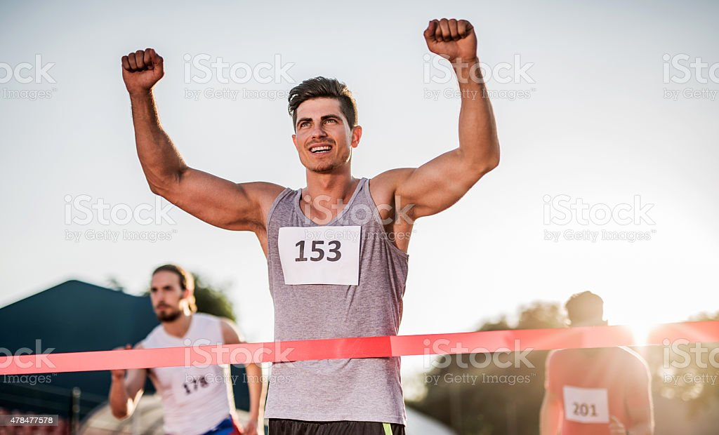 Successful athlete crossing the finish line and winning the race. stock photo