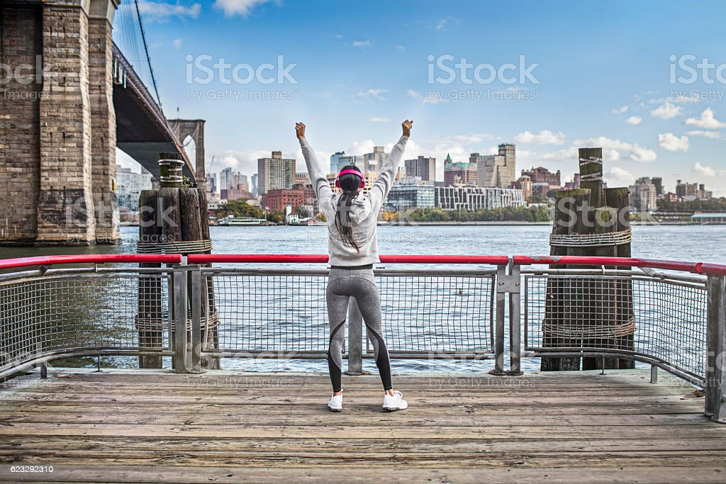 Successful athlete on boardwalk by Brooklyn Bridge stock photo