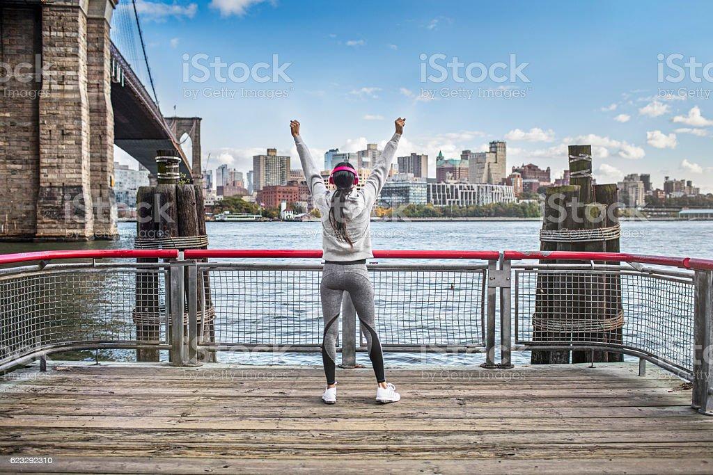 Successful athlete on boardwalk by Brooklyn Bridge stock photo