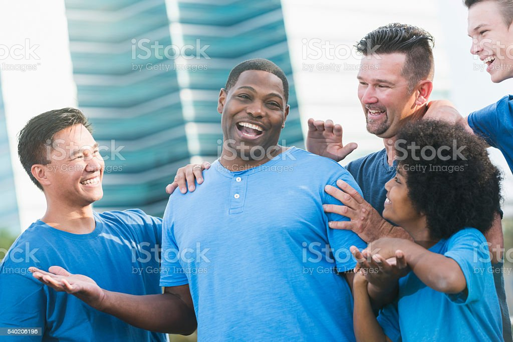 Successful black man getting pat on back from friends stock photo