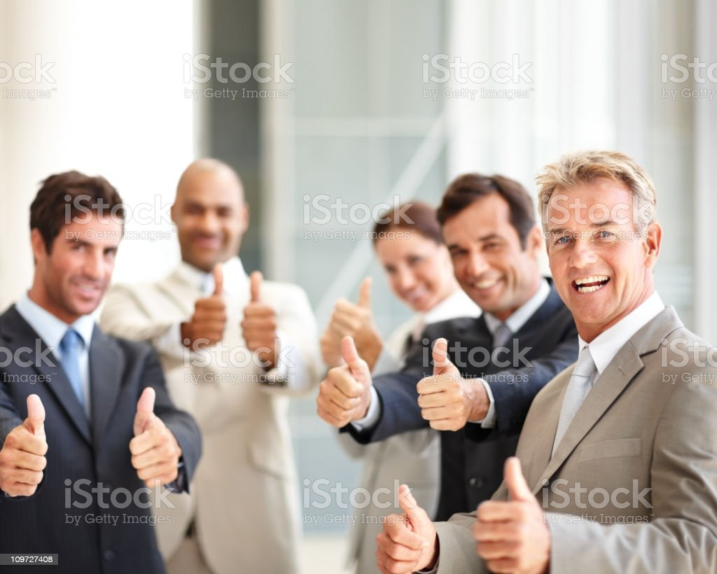 Successful business colleagues showing thumbs up sign royalty-free stock photo