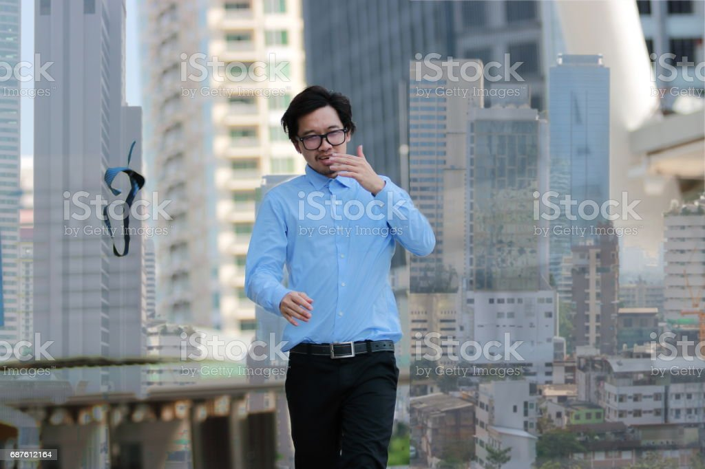 Successful business concept. Double exposure of happy young Asian businessman walking and throwing his necktie in urban building city background. stock photo