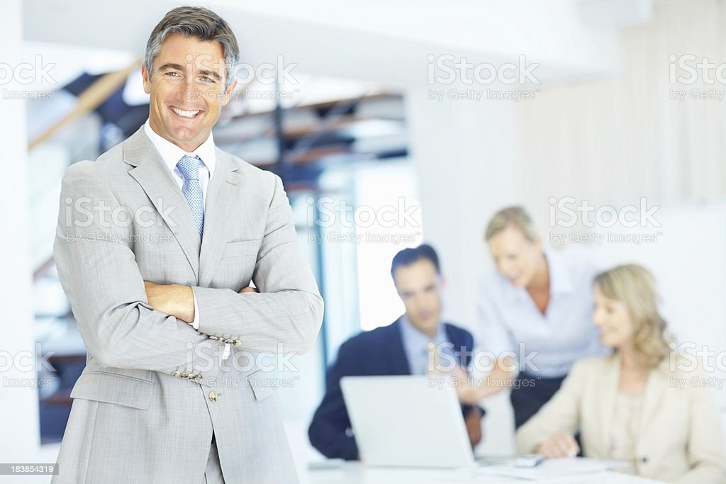 Successful business man with his team in the background royalty-free stock photo