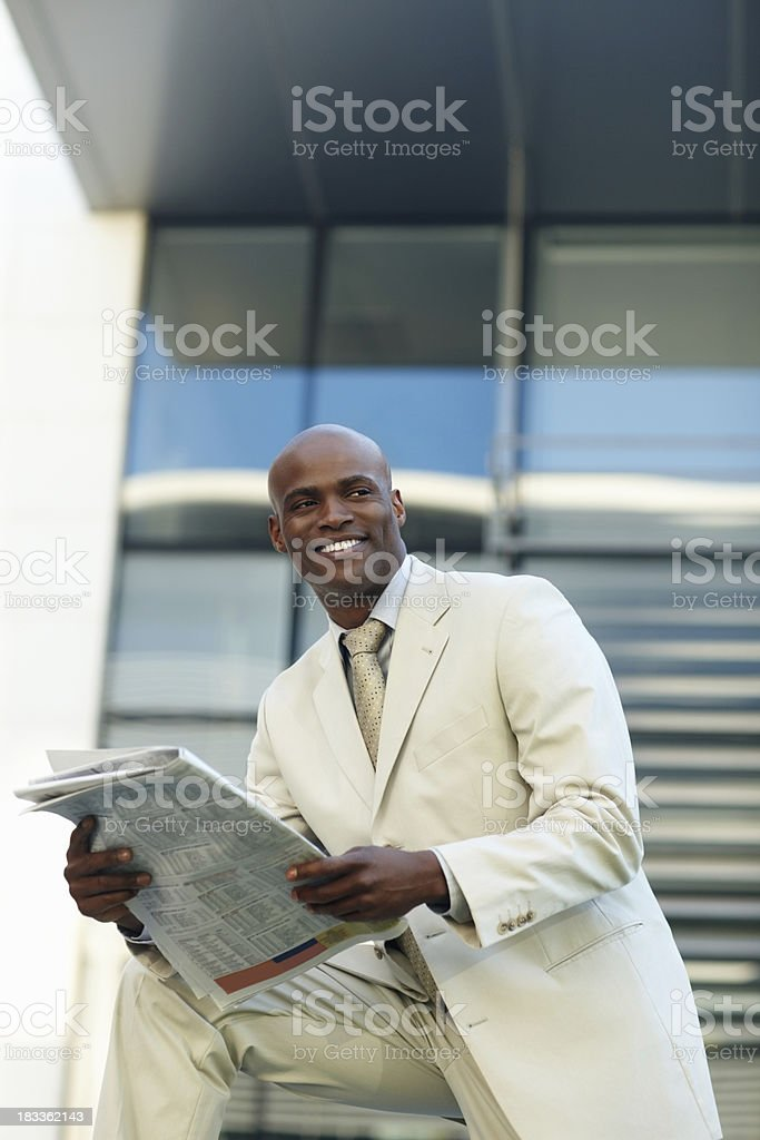 Successful business man with newspaper royalty-free stock photo