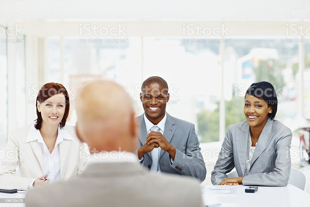 Successful business people conducting interview of a senior man royalty-free stock photo