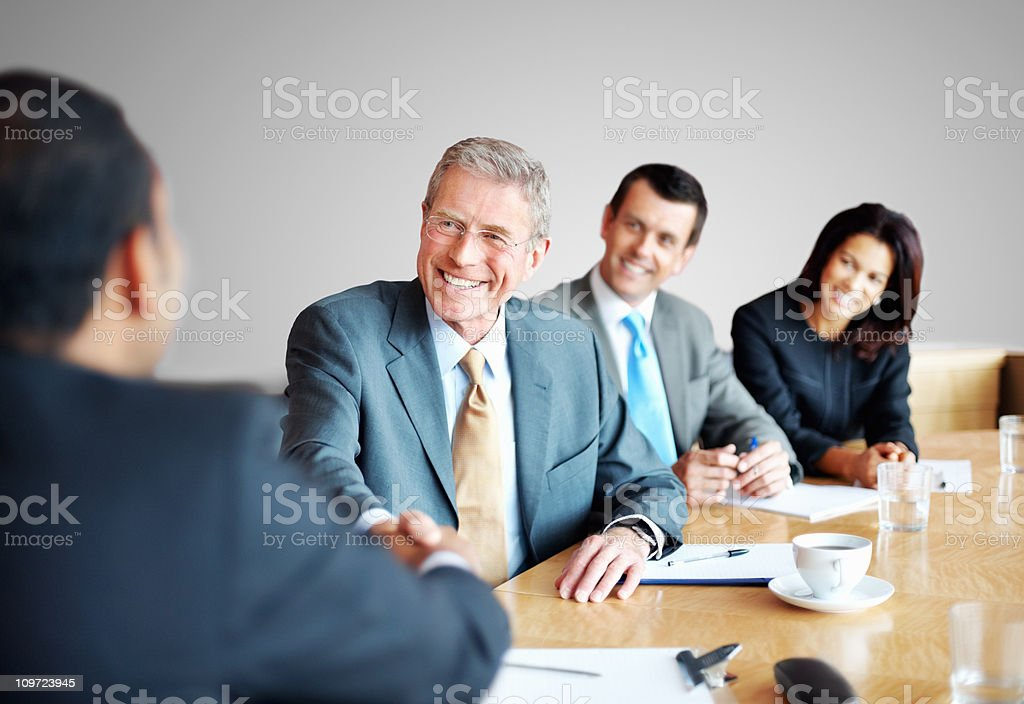 Successful business people shaking hands in a meeting at office stock photo