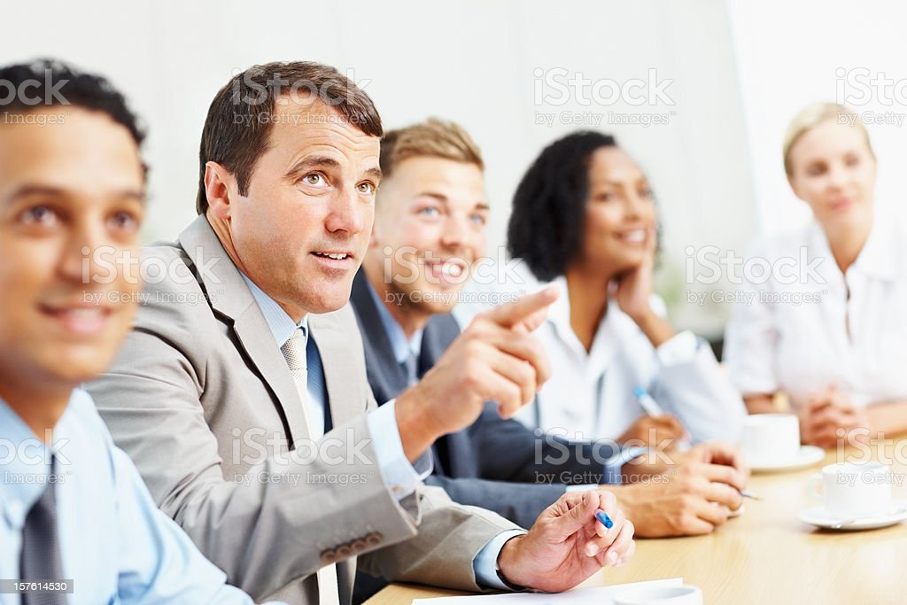 Successful business people sitting in discussion at a meeting royalty-free stock photo