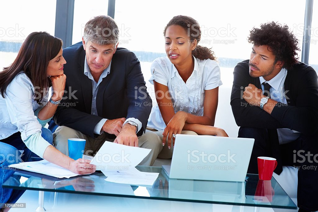 Successful business team sitting together and working on a laptop stock photo