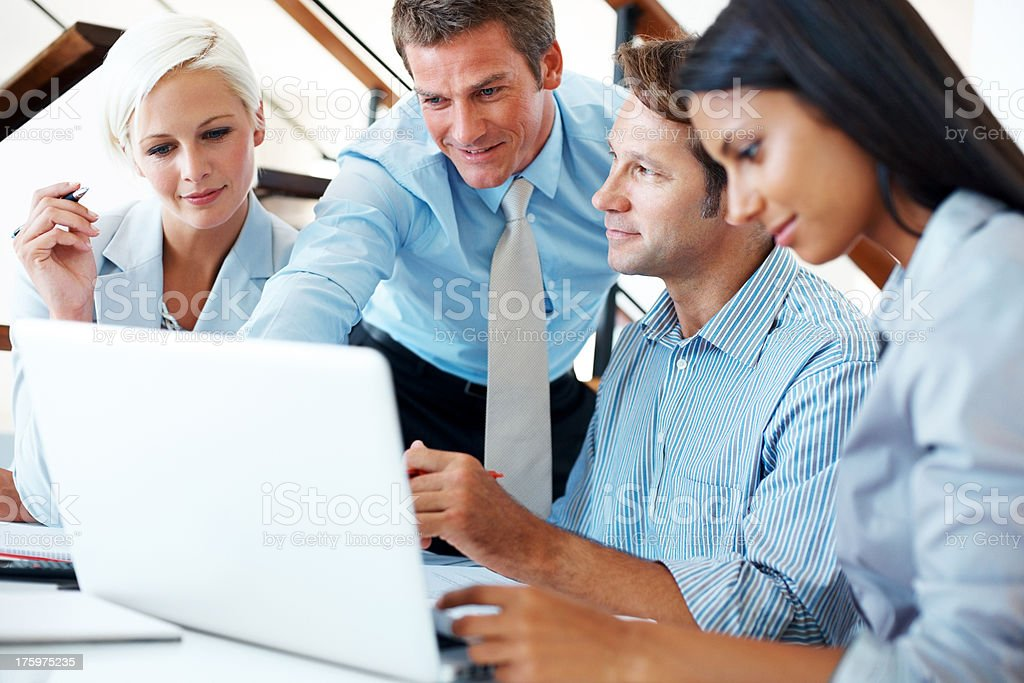 Successful business team working together on laptop stock photo