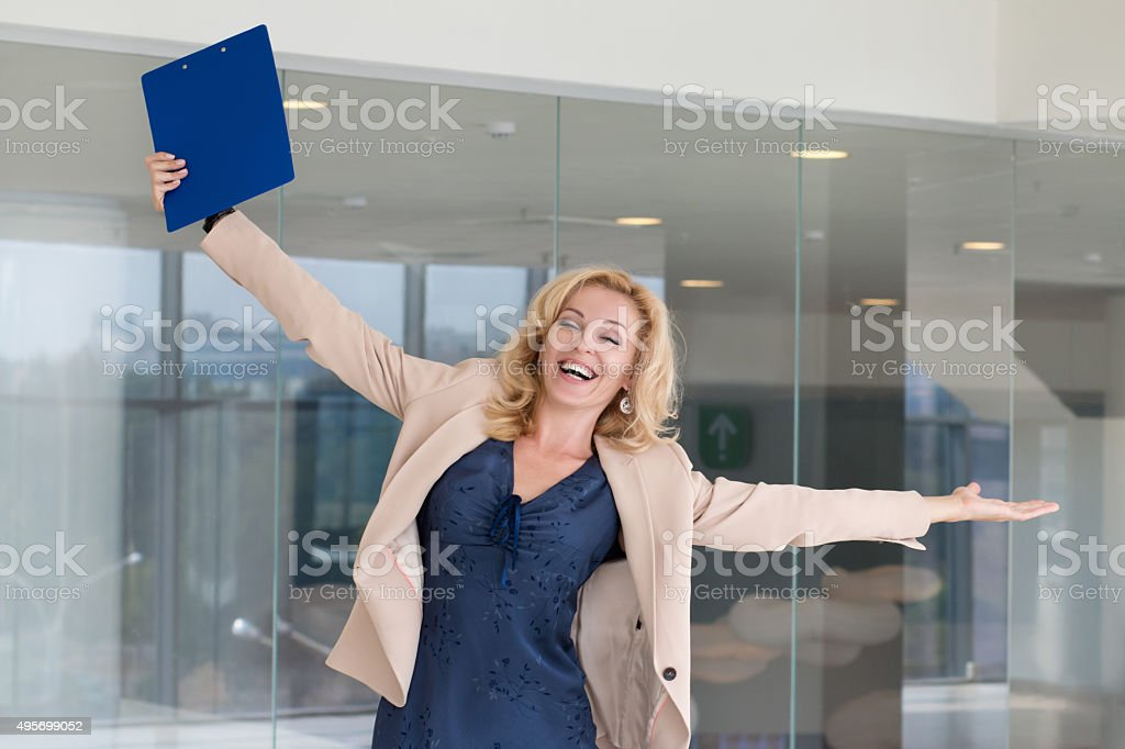 Successful business woman celebrating with arms up stock photo