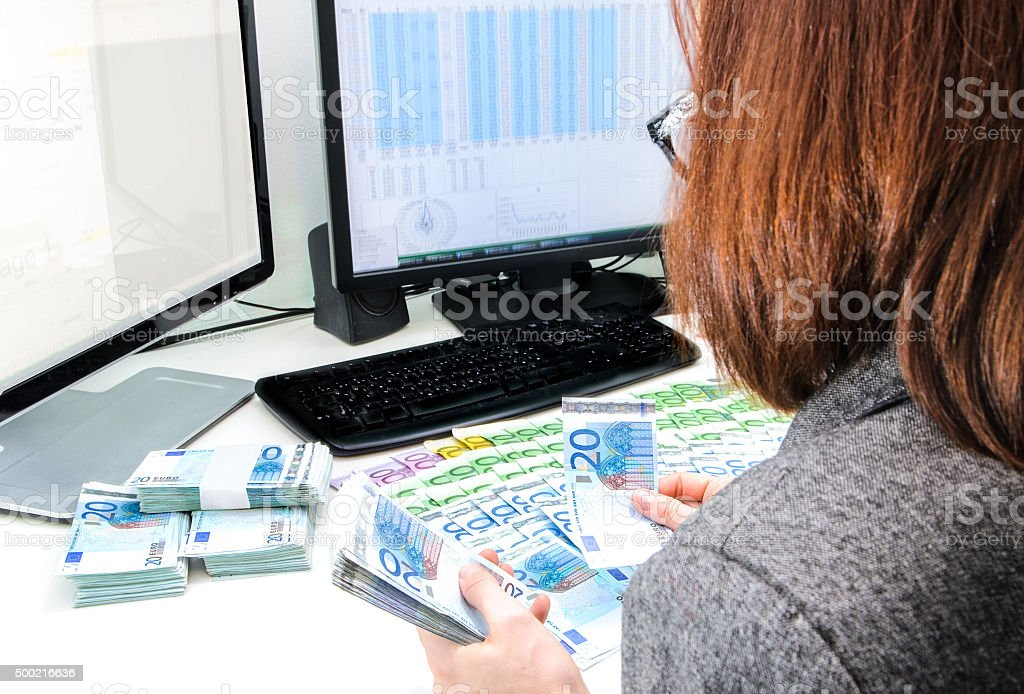 Successful business woman is counting money bills ona a desk stock photo