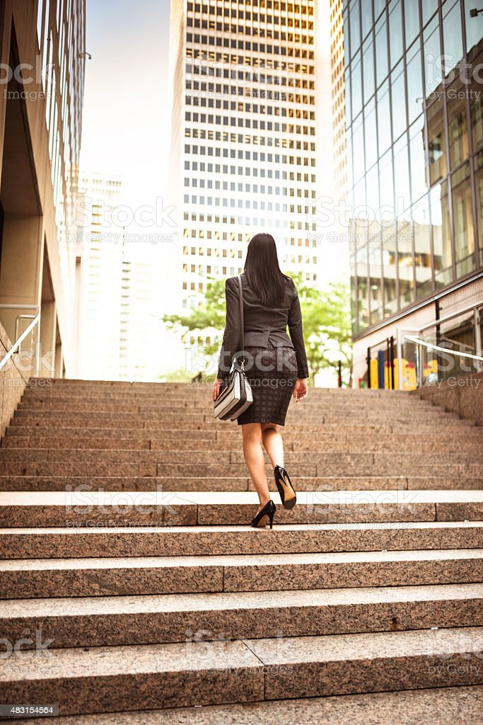 successful business woman moving up the staircase stock photo