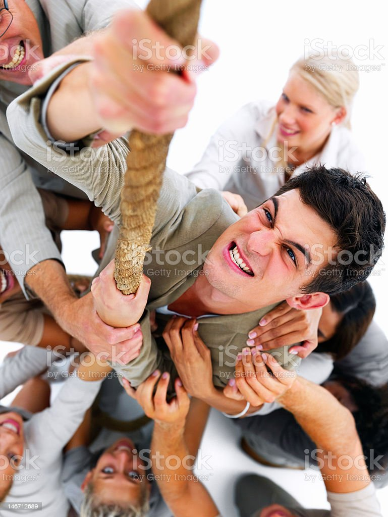 Successful businessman climbing a rope surrounded by colleagues royalty-free stock photo