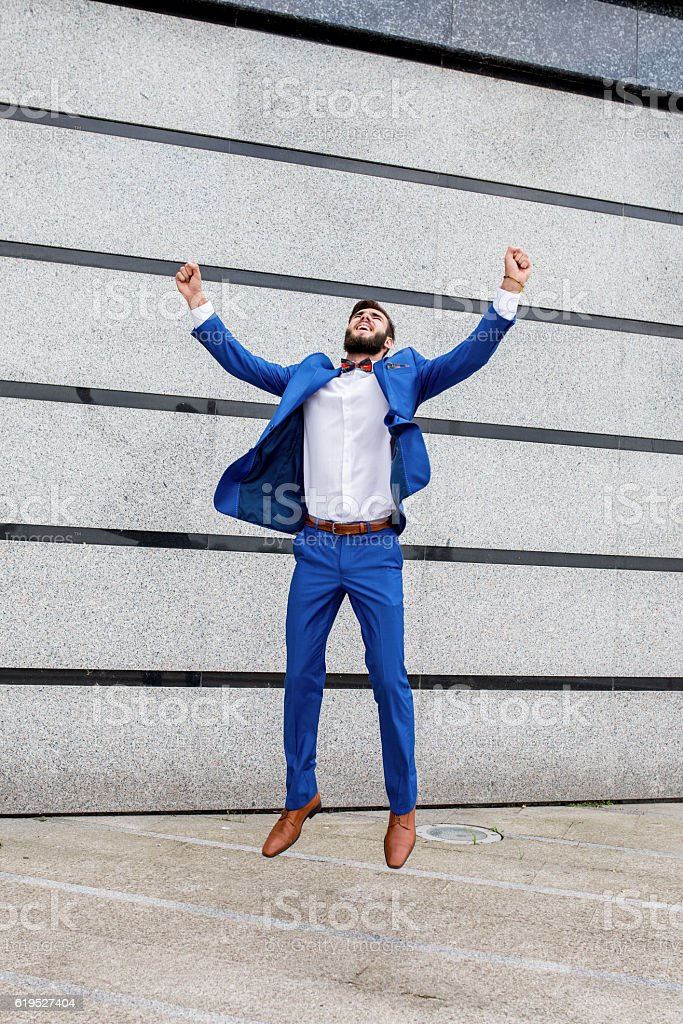 Successful businessman jumping on the street and celebrating. stock photo