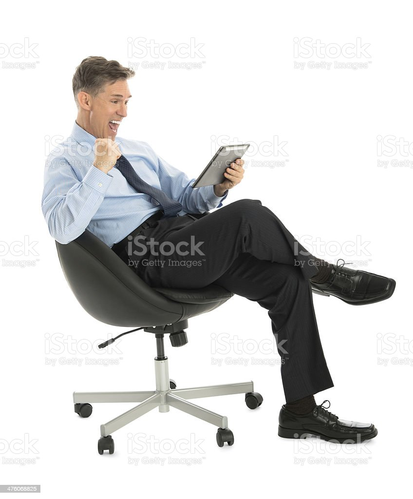 Successful Businessman Looking At Tablet While Sitting On Office royalty-free stock photo