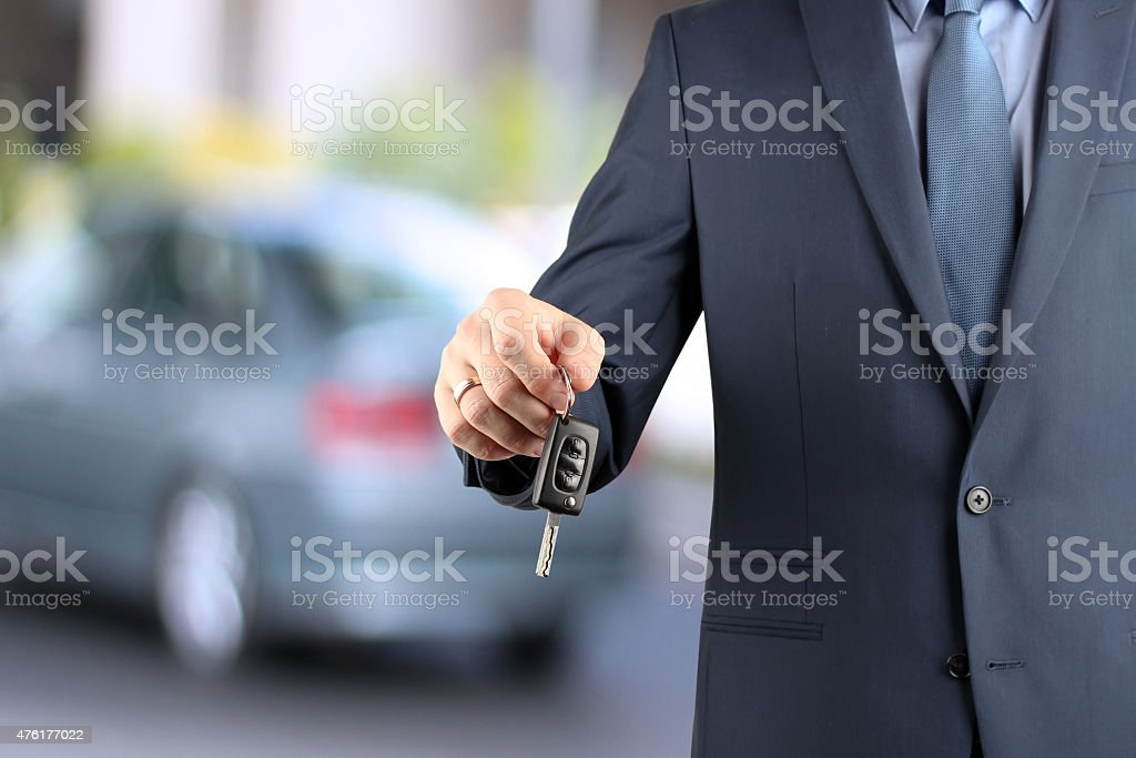 Successful businessman offering a car key. Driver's hand showing key stock photo