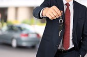 Successful businessman offering a car key. Driver's hand showing key