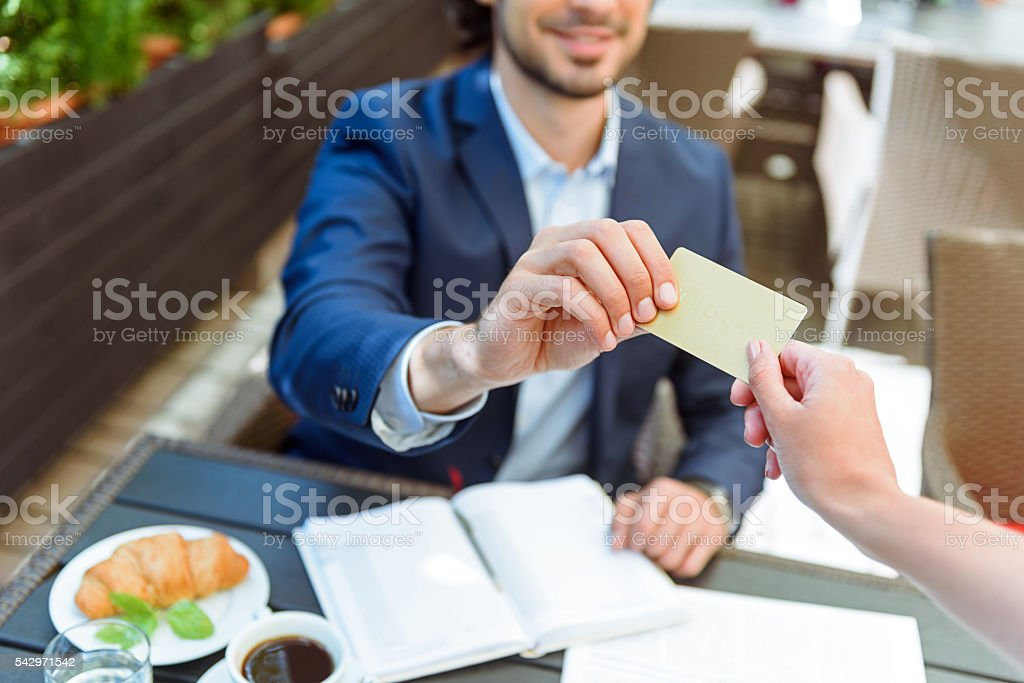 Successful businessman paying bill in cafe stock photo