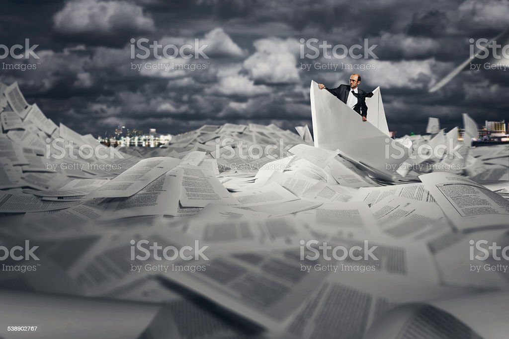Successful businessman sailing on paper boat stock photo
