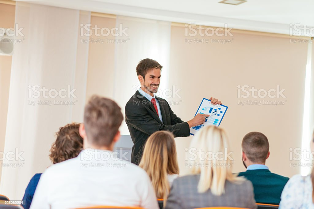 Successful businessman showing charts to seminar participants stock photo