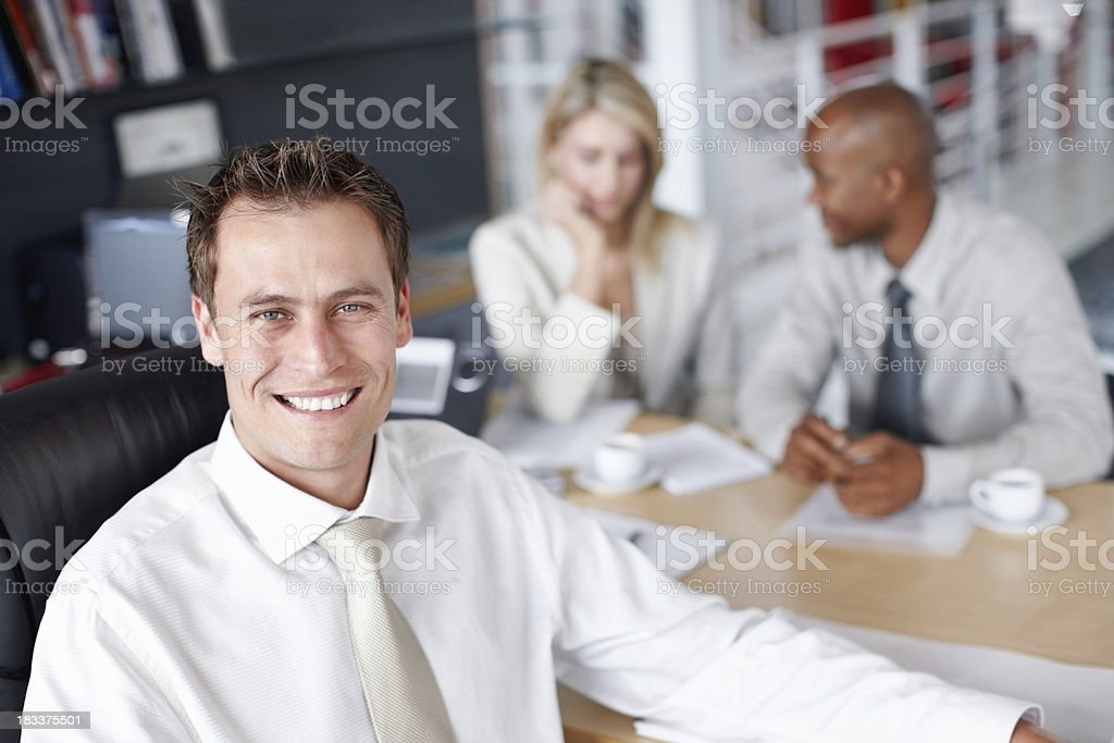 Successful businessman smiling with colleagues in background royalty-free stock photo