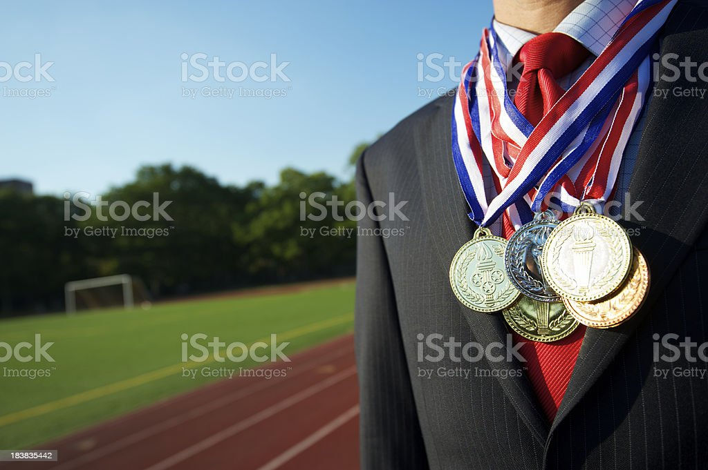 Successful Businessman Standing Decorated with Medals by Running Track stock photo