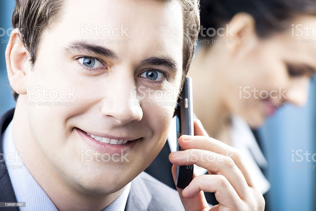 Successful businessman with cellphone and colleague, at office royalty-free stock photo