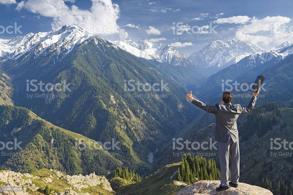 Successful businessman with laptop at the top of mountain royalty-free stock photo