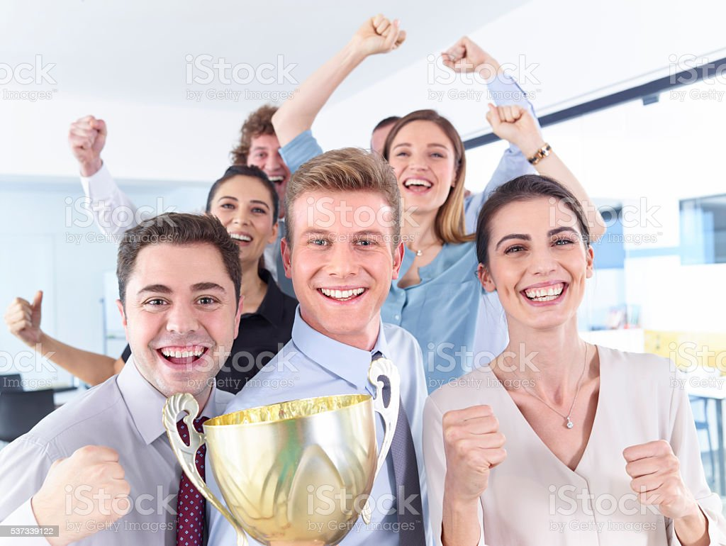 Successful businesspeople celebrating with the cup in hands stock photo