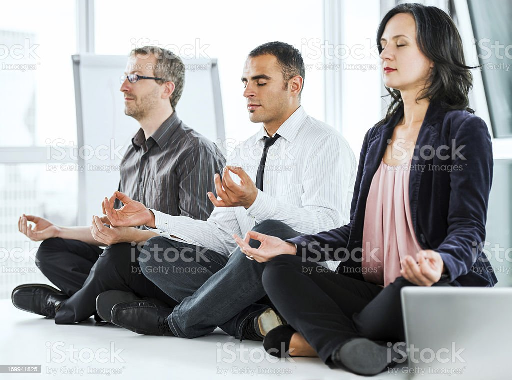 Successful businesspeople meditating in the office. royalty-free stock photo