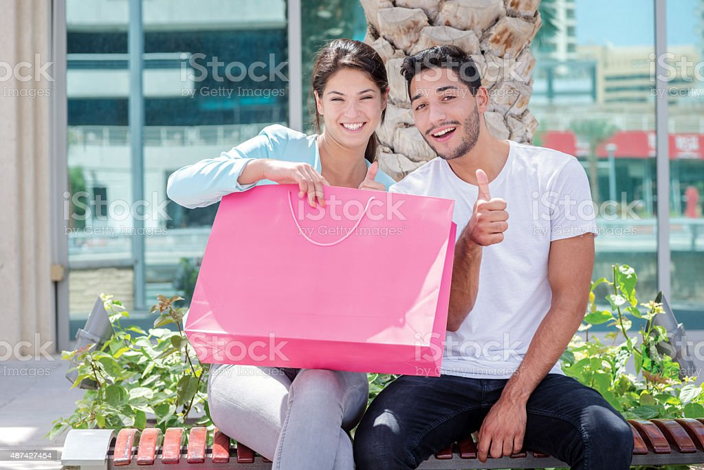 Successful collaborative shopping. Couple sitting on a bench and stock photo