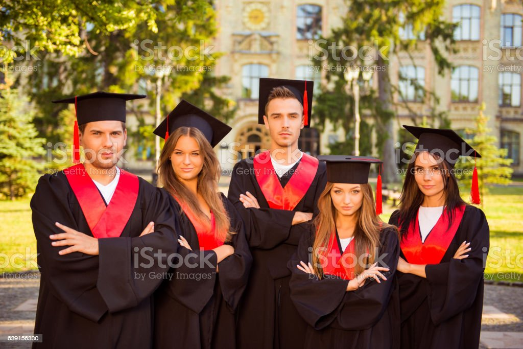 successful confident graduates in robes and hats crossing hands stock photo