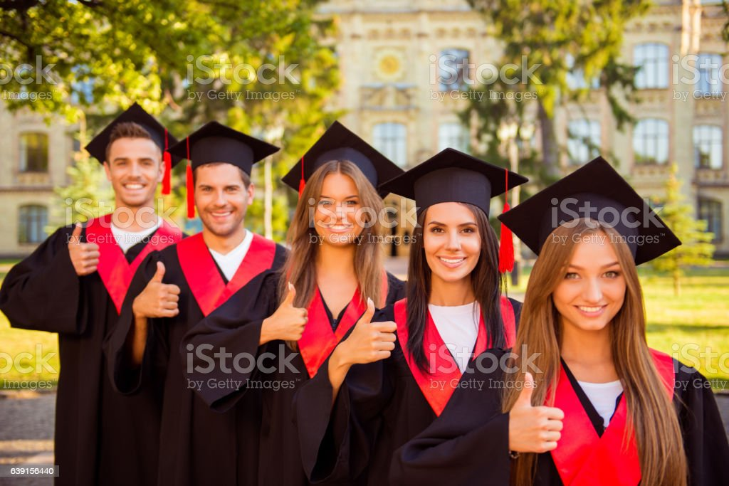 successful confident graduates in robes and hats showing thumbs up stock photo
