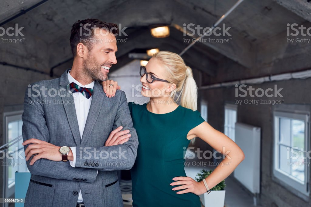 Successful couple, business partners looking at each otcher at modern office stock photo