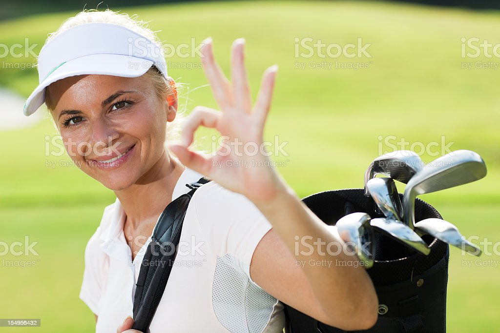 Successful female golf player showing okay. royalty-free stock photo