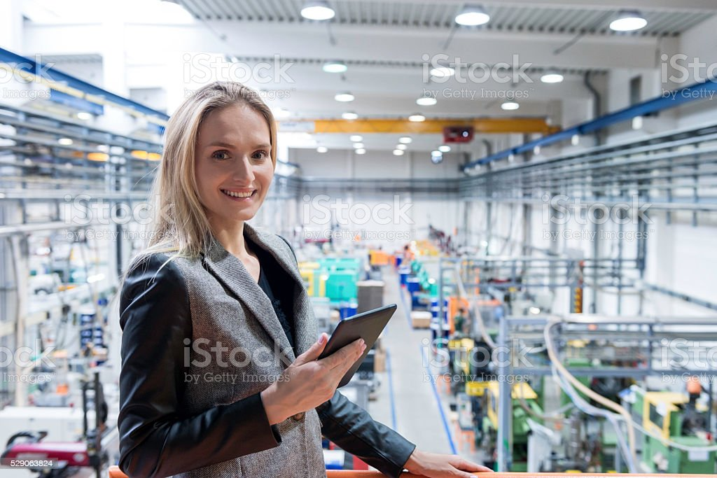 Successful female with tablet in futuristic plant stock photo