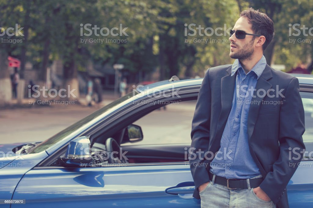 Successful handsome young man standing by his new car enjoying summer day stock photo
