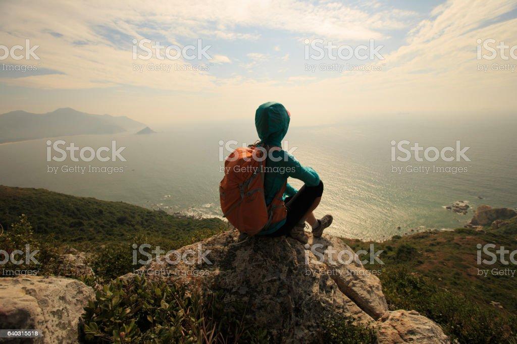 successful hiker on seaside mountain peak rock stock photo
